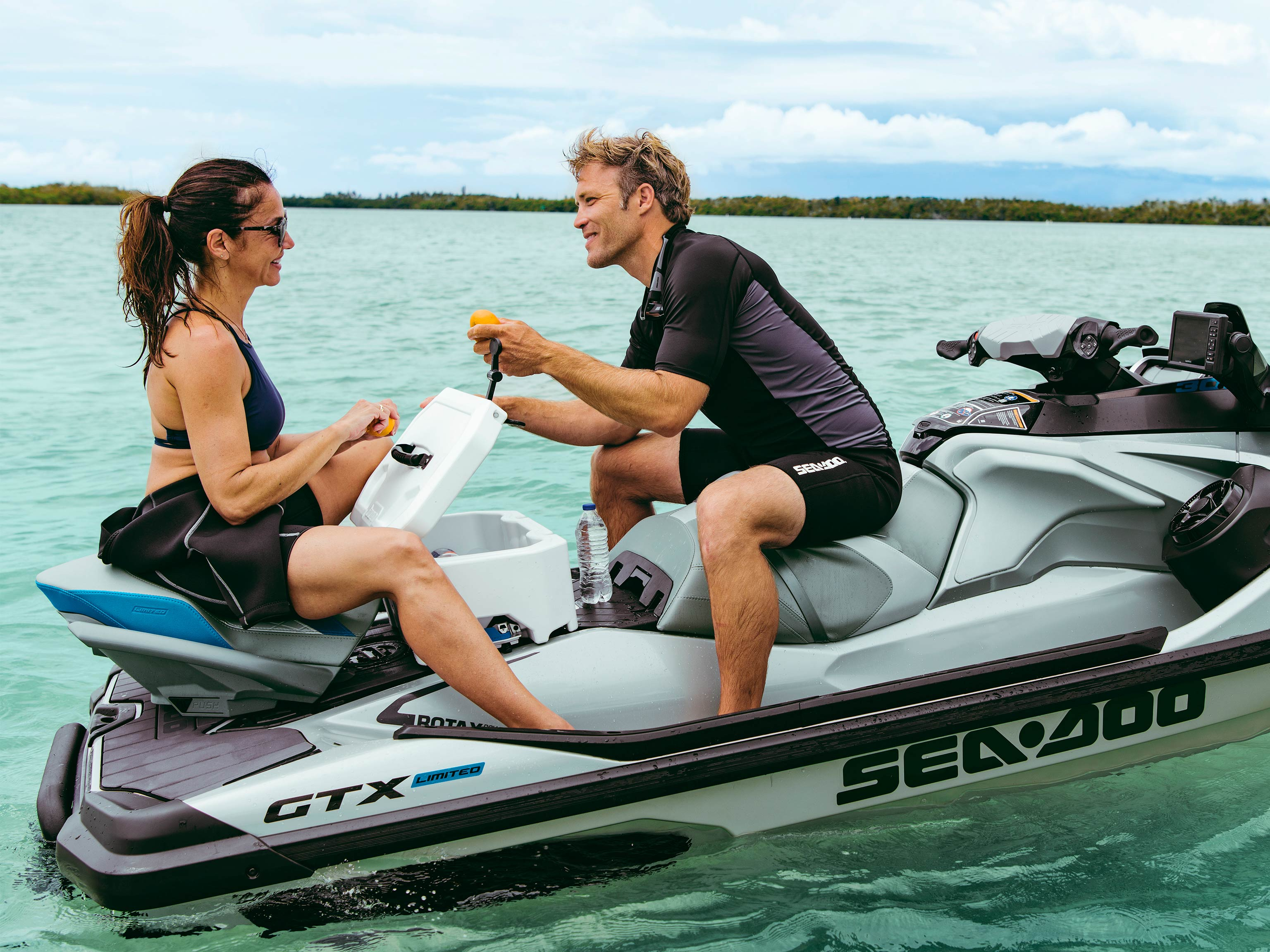Couple sharing an orange on a Sea-Doo GTX
