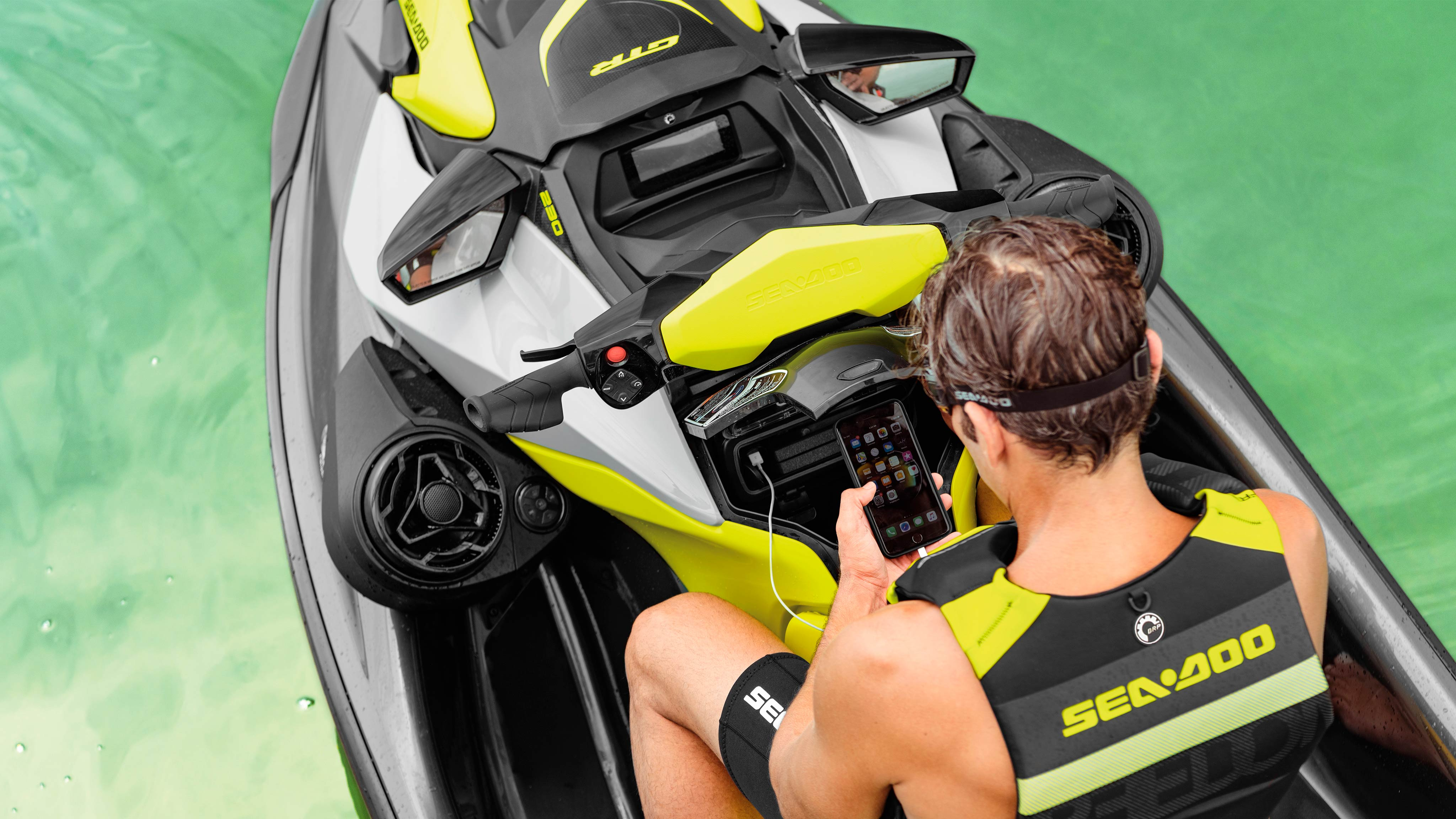 Man sitting on a Sea-Doo GTR looking at his phone