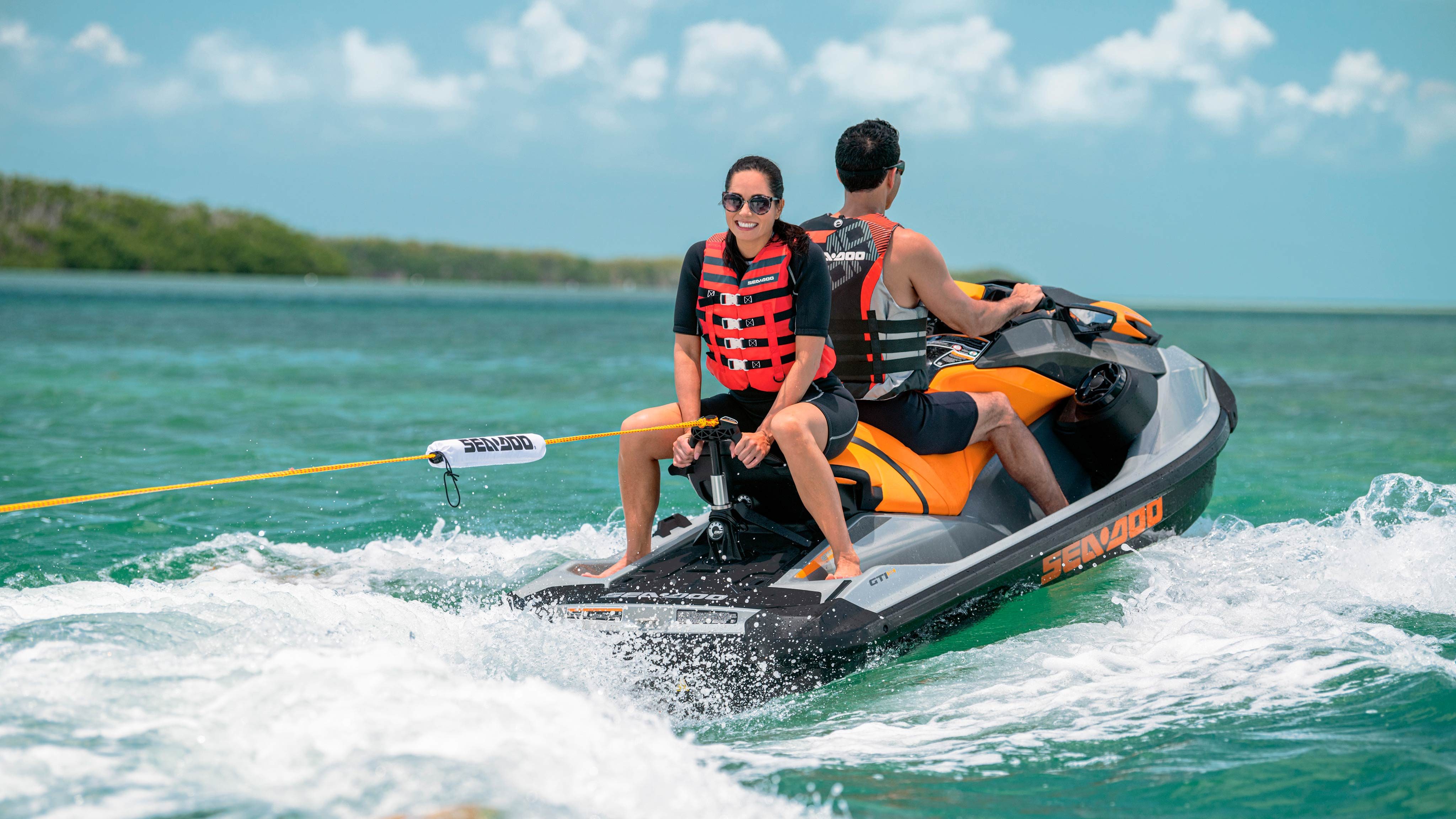 A couple riding on a Sea-Doo GTI SE and pulling their kid behind