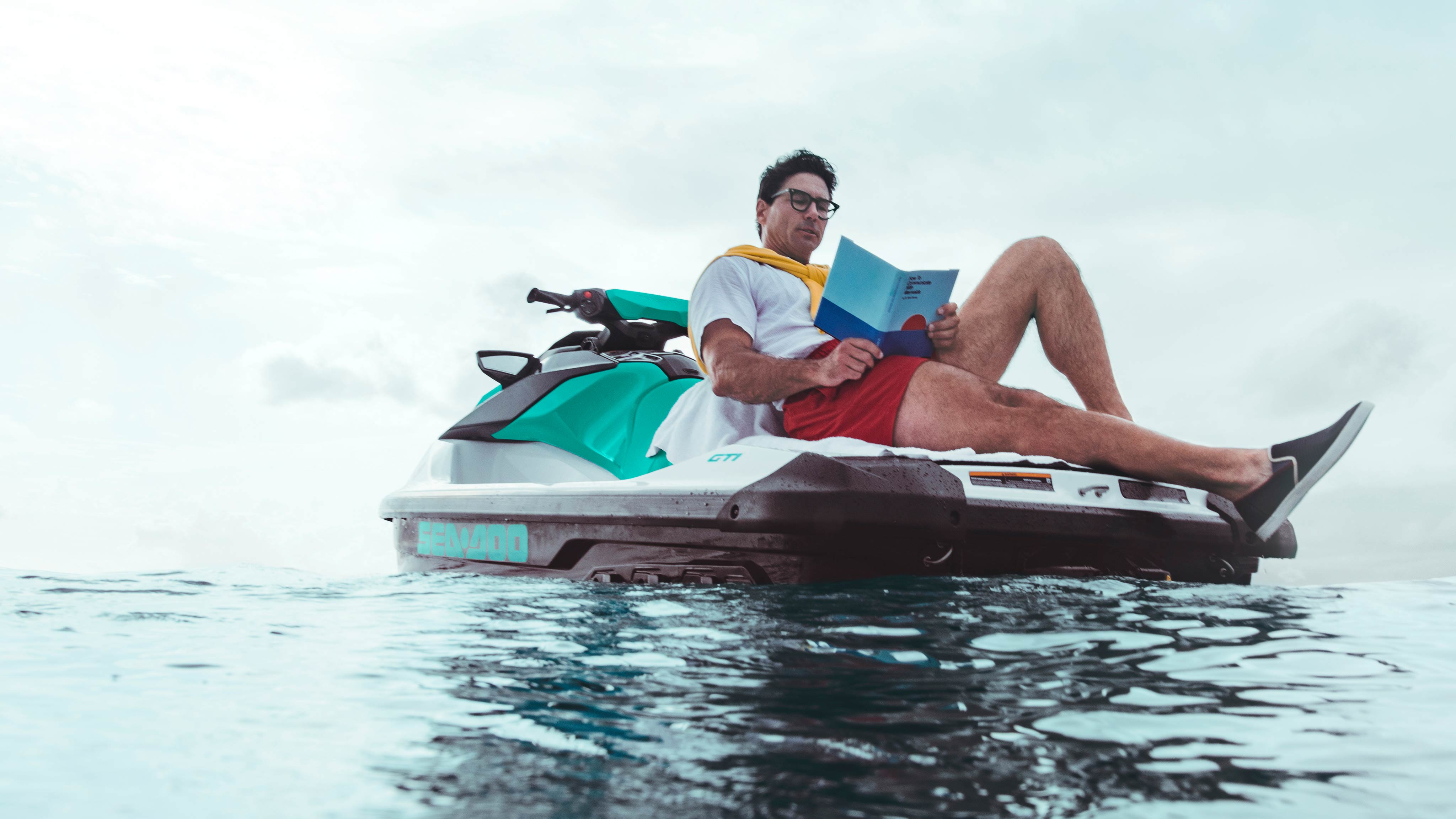Man reading a book from the Sea-Doo GTI back swim platform