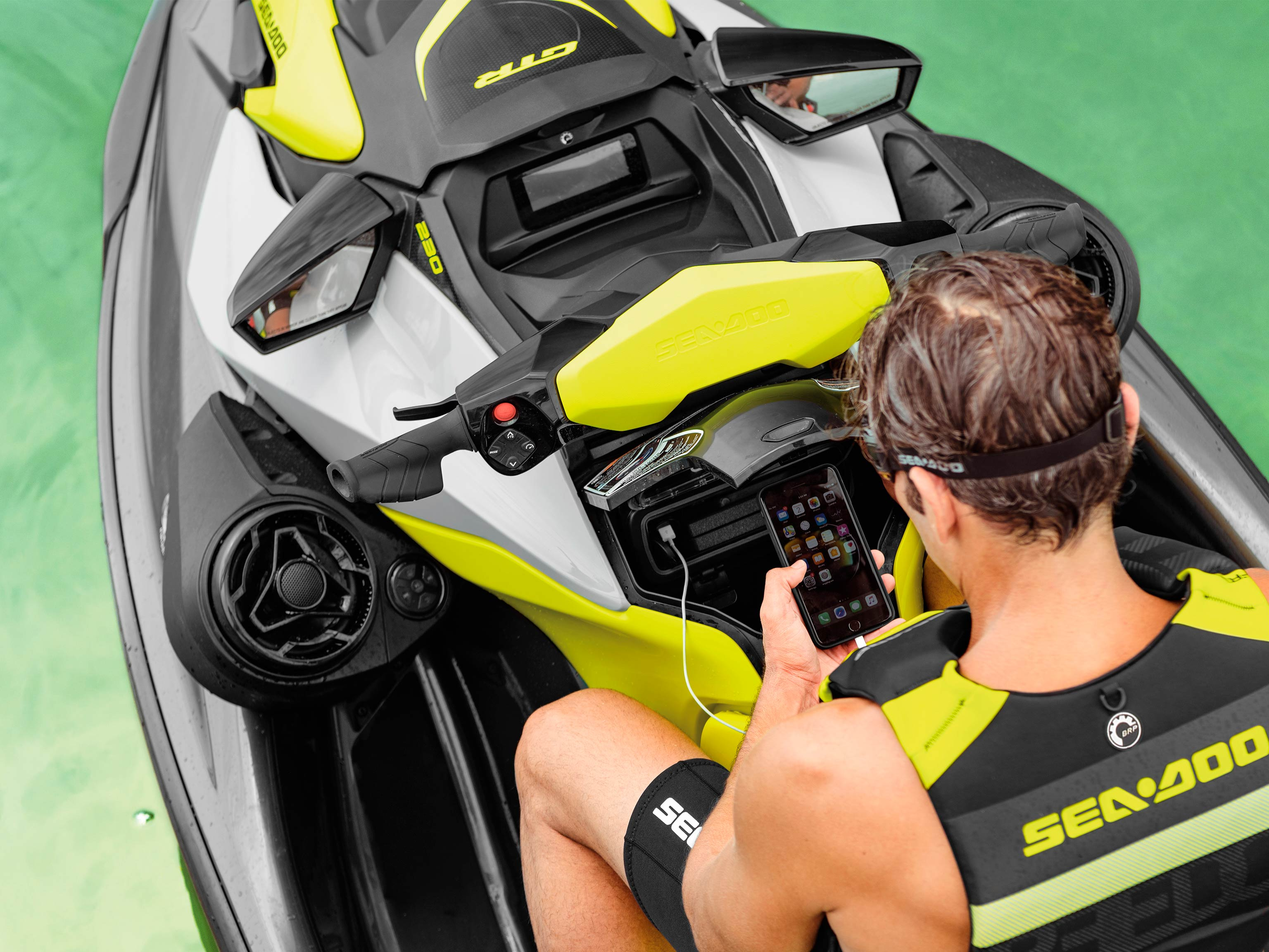 Man looking at his cell phone on a Sea-Doo