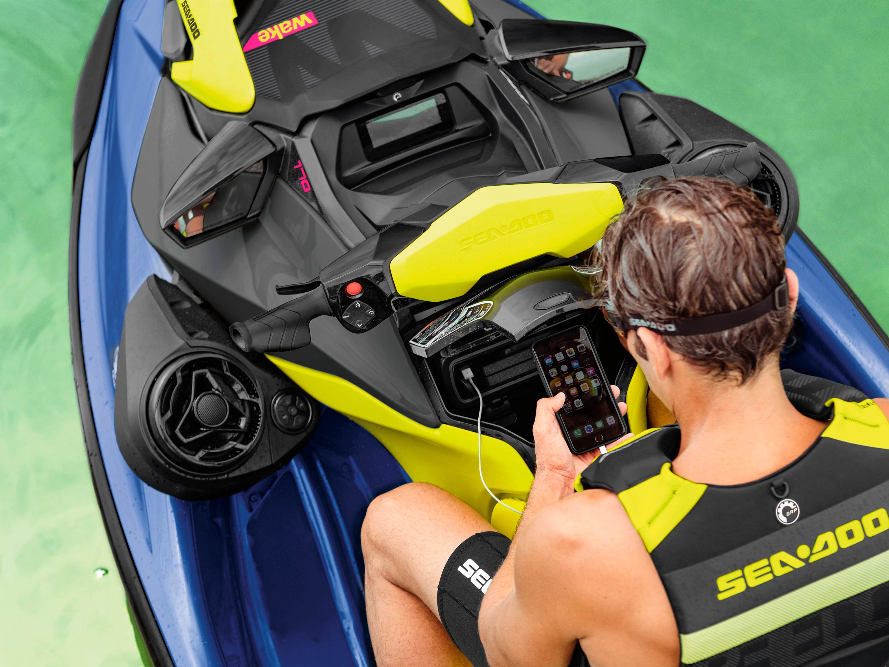 Men looking at his phone on a Sea-Doo WAKE PRO