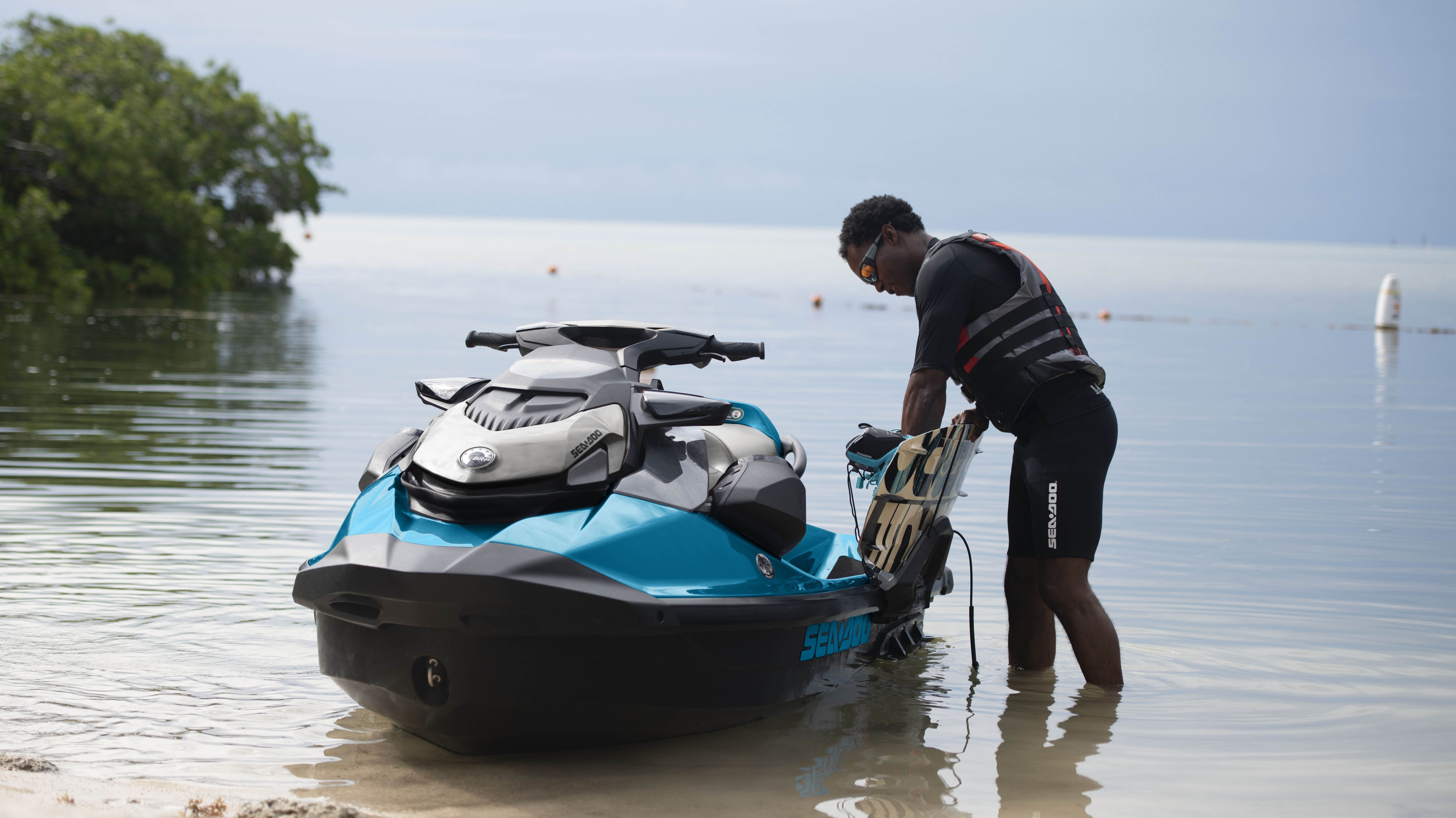 Man fixing wakeboard on the Sea-Doo GTI SE