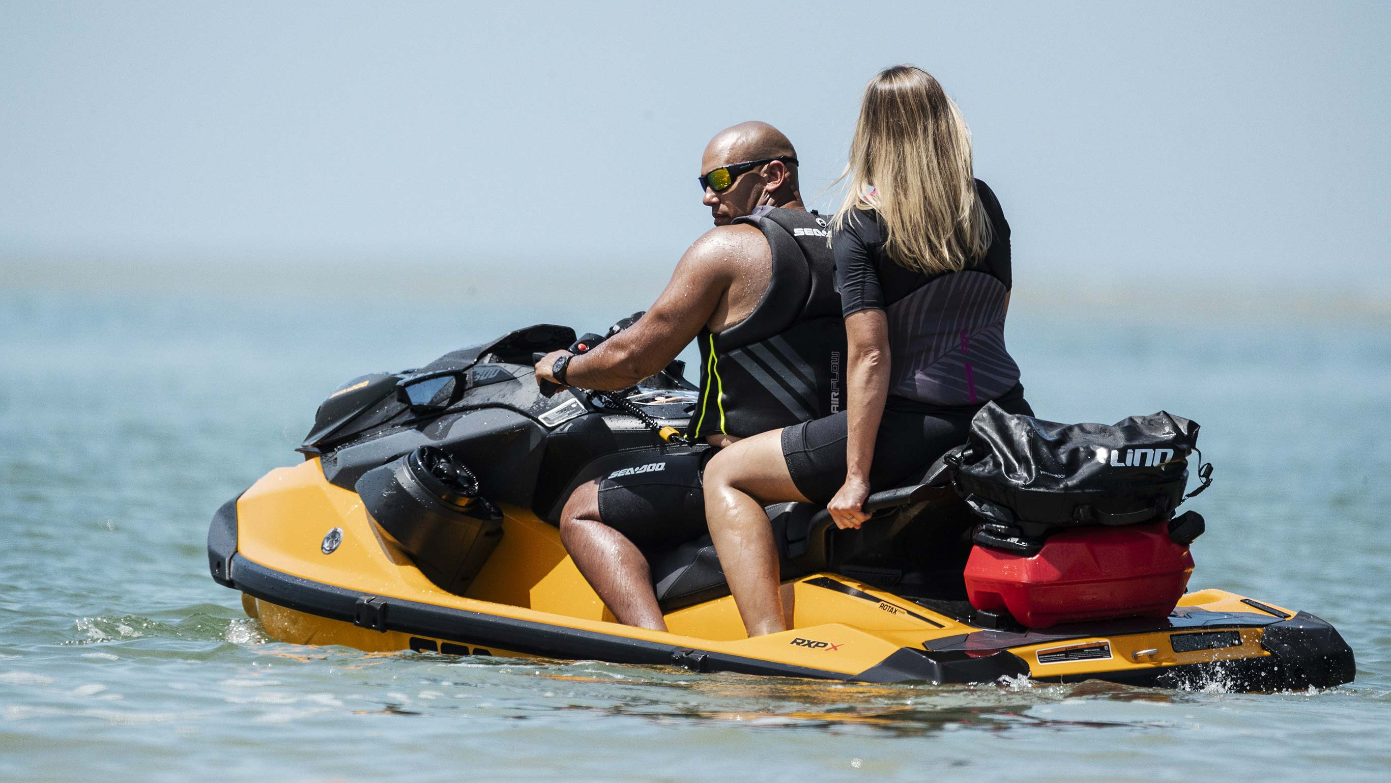Couple riding a Sea-Doo RXP-X with a LinQ system