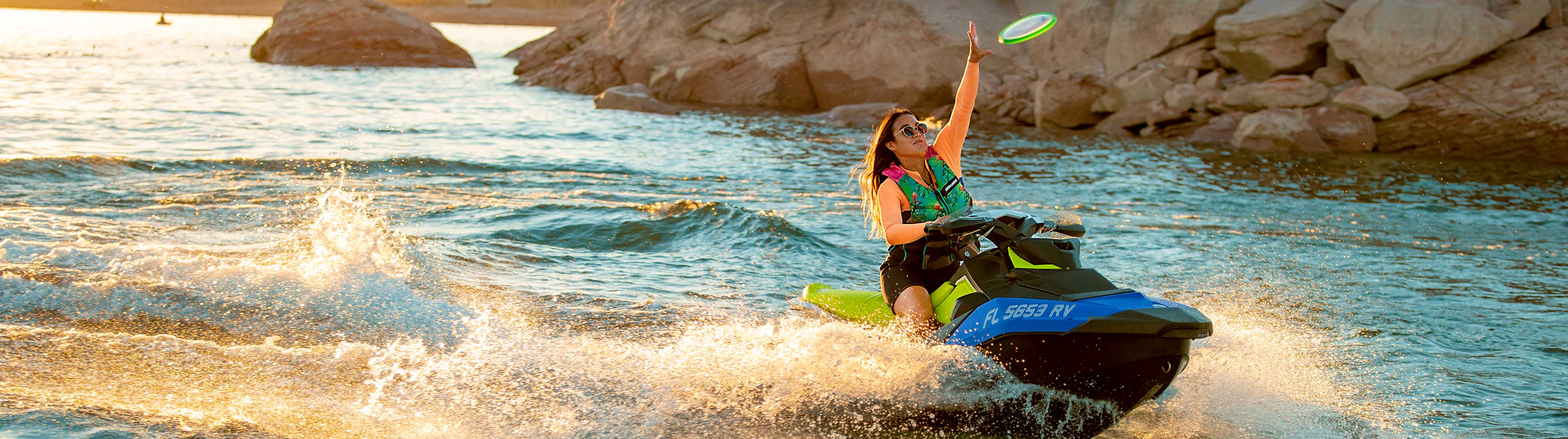 Women driving a Sea-Doo SPARK while catching a Frisbee
