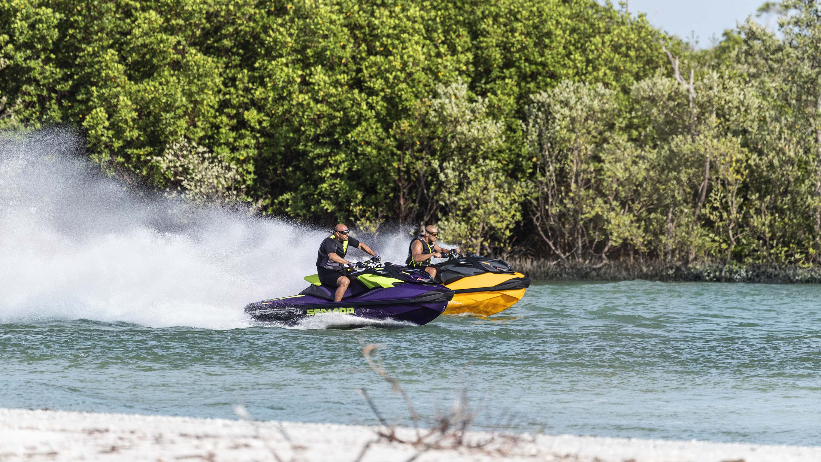 Two men riding Sea-Doo watercrafts very fast